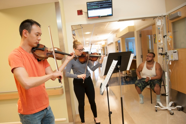 Medical student Joshua Rim and Dona Occhipinti of Welch Allyn perform for Aaron Johnson, a patient. (PHOTO BY SUSAN KAHN)