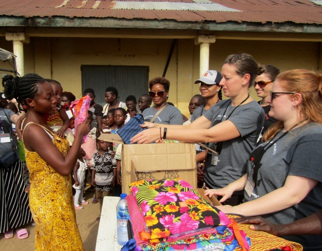 Upstate nurse Meghan Lewis gives a Days for Girls reusable menstrual kit to a young mother at a market in Kumasi, Ghana. (PHOTO BY SUSAN KEETER)