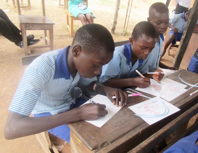 These young men are making their books during the literacy program. They walk four hours to attend school in an outdoor classroom with a dirt floor and metal roof supported by tree branches. (PHOTO BY SUSAN KEETER)