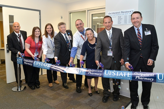 Cutting the ribbon to open the Upstate outpatient pharmacy are, from left, Upstate University Hospital Interim CEO Robert Corona, DO; Pharmacy Technician Stephanie McDevitt; Pharmacist Emily Adamy; Pharmacy Director Luke Probst; Pharmacist David Geloso; Upstate Medical University President and Health System CEO Danielle Laraque-Arena, MD; Associate Director of Pharmacy Enterprise Eric Balotin; and Upstate Chief Financial Officer Stuart Wright. (Photo by Debbie Rexine)