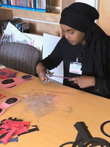 Muno Nuur, a Le Moyne College student, at work in the Family Resource Center at the Upstate Golisano Children's Hospital. (Photo by Amani Mike)
