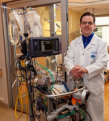 Christopher Tanski, MD, with the ECMO machine. (Photo by William Mueller)