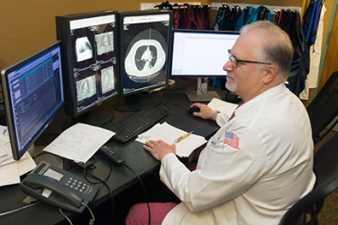 Karmel reviews a CT scan of a chest to evaluate whether fluid around the lung needs to be drained. (photo by Richard Whelsky)