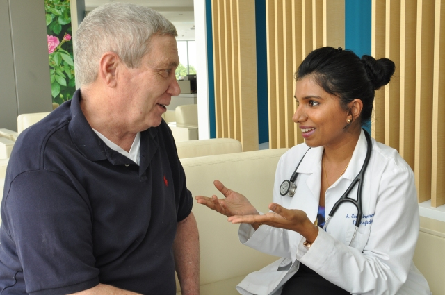 Eugene Young talks with his oncologist, Abi Siva, MD, about encouraging results of immunotherapy medication. (photo by Richard Whelsky)