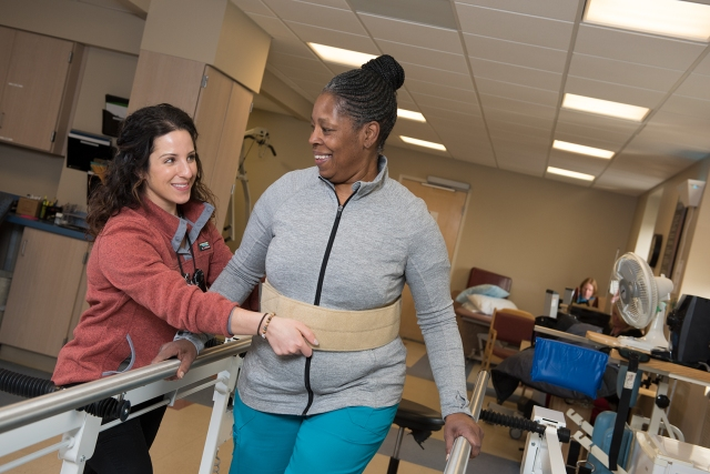 Physical therapist Nicole Conese, left, and Karen Renfroe demonstrate walking with a back support in the rehabilitation center at Upstate University Hospital's Community campus. (photo by Susan Kahn)