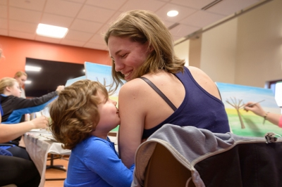Alayah Green, 4, kisses her mom, Katie Green, while she and other mothers of cancer patients paint landscapes at the H.O.P.E. art session led by Ally Walker.