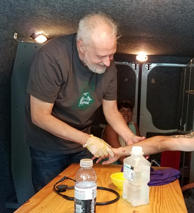 Using a van as a patient room, Lehmann examines a homeless man's wounds. (photo by Robert Mescavage)