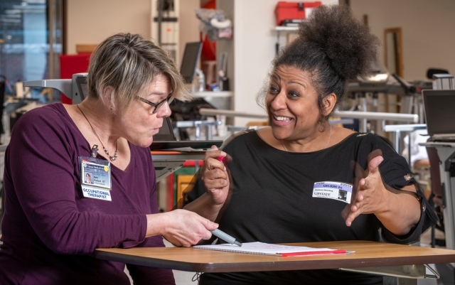 Occupational therapist Beth Rolland, left, with stroke rehabilitation patient Melissa Meloling, during a therapy session. (photo by Robert Mescavage)