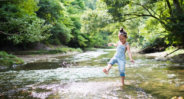 Little girl playing on a stream