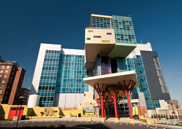 """From the outside, the Upstate Golisano Children's Hospital looks as though it was snapped together with brightly colored toys. To enter, you walk past the red trunks of several """"trees"""" holding up the roof and into elevators that go directly to the """"treehouse"""" on the 11th and 12thfloors. (photo by Robert Mescavage)"""
