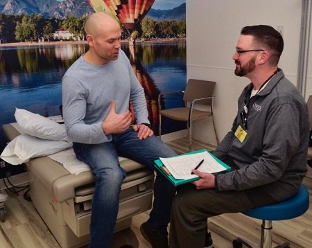 Kosick, left, speaks with nurse Christopher White, part of the Survivor Wellness Program team, during an annual visit to the Upstate Cancer Center. (photo by Debbie Rexine)