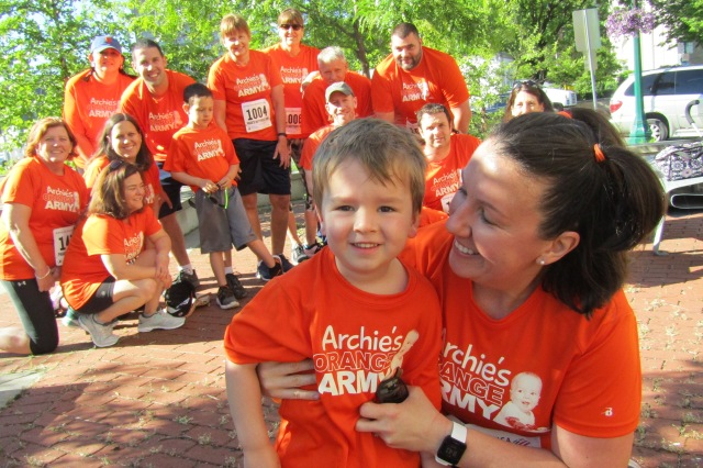 "One of the organizations that helped Archie Kulkus (in the foreground with his mother, Emily) and his family during his cancer treatment was Paige's Butterfly Run, which has raised more than $3 million to help kids and their families in Central New York. His family and friends participate in the annual run as members of ""Archie's Orange Army."" Emily Kulkus works in public and media relations at Upstate. (photo by Susan Keeter)"