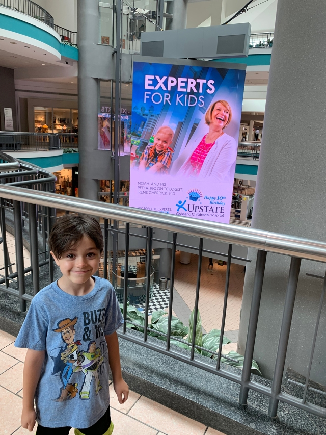 Noah Axtell, standing by a poster showing him with Upstate pediatric cancer specialist Irene Cherrick, MD. (provided photo)