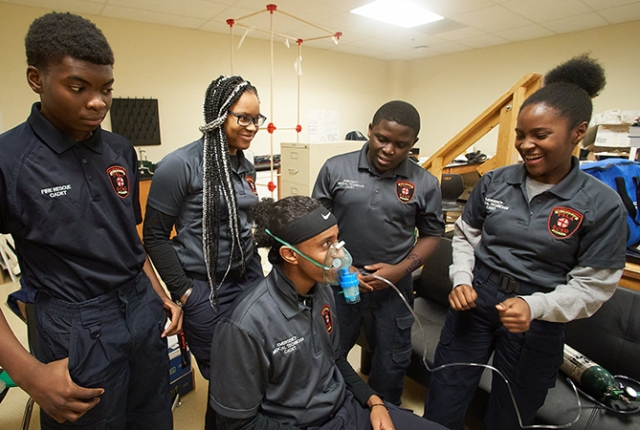"""Learning to administer a breathing treatment is important — and fun — for these future emergency medical technicians. Standing, from left, are Fowler High School students Bishop Walden, Nye'Kerria Dorsey, Eriya Ndayambaje and Furaha Nyirarugendo. The """"patient"""" wearing the mask is EMT student Najib Ahmed. (photos by Chuck Wainwright)"""