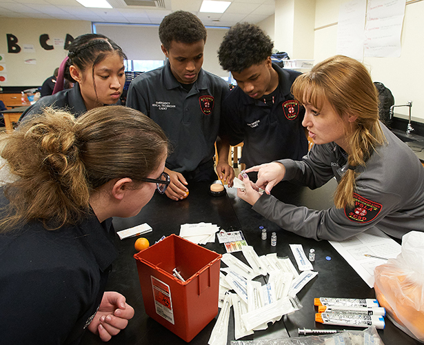 Brandi Schaefer, right, prepares students to give injections, which they practice using oranges. Pictured, clockwise from left, are Alex Jones, Mya Aung, Ridwan Sirad and Hussein Musa.