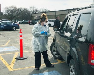 Upstate nurse Julia Burns greeted a patient at the coronavirus testing site at the Upstate Specialty Services at Harrison Center. To minimize contact, gowned and masked staff took nasal swabs in the parking lot, so patients did not have to leave their vehicles. The swabs were tested for dozens of respiratory illnesses in the pathology lab at Upstate. If those were negative, the swabs were sent to Albany for coronavirus testing. (photo by Susan Keeter)