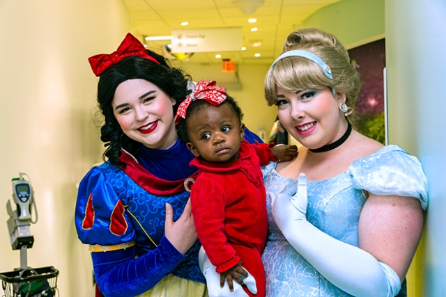 Nine-month-old Maryangeliz Rodriguez, of Syracuse met Snow White and Cinderella during her brother Michael's appointment at Upstate's Waters Center for Children's Cancer and Blood Disorders. The Disney princesses are from the Moment of Magic Foundation. Michael went home with a free book after his appointment. (photo by William Mueller)